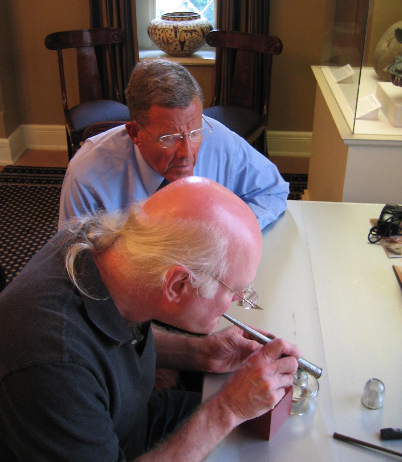 Daniel demonstrates blowpipe analysis of metallic ore for the secretary of the Smithsonian Institution.