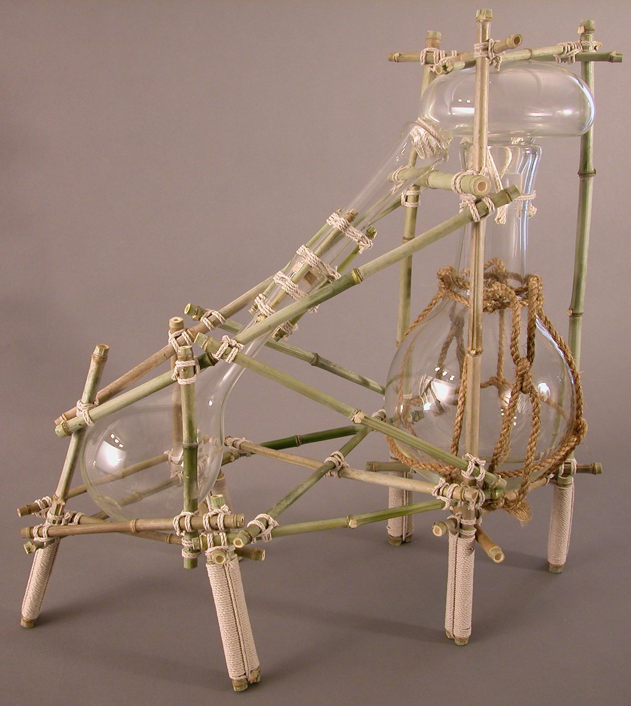 Bamboo and glassware sculpture, set up to display distillation.